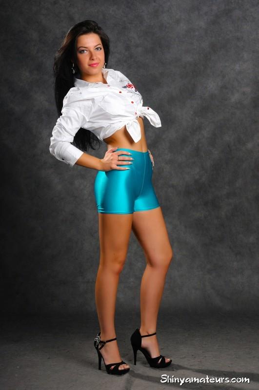 burnette woman Marina E in cyan lycra shorts & high heels